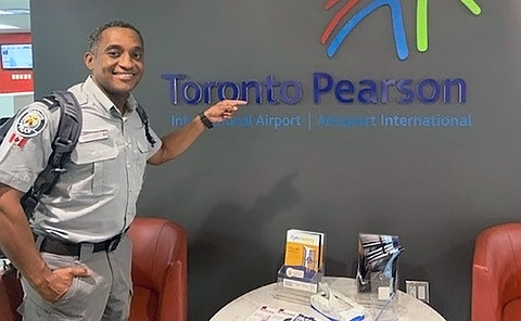 Man in a police uniform standing in a lounge and pointing at a sign Toronto Pearson International Airport