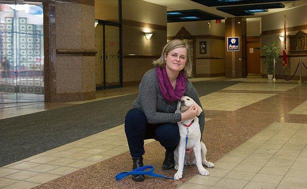 A woman kneeling next to a labrador puppy