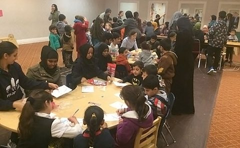 Large group of children and adults sitting at tables writing or painting
