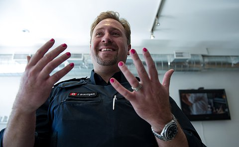 An officer looking at his pink nails and smiling.