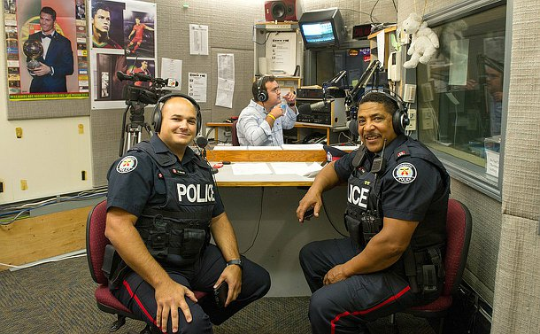 Two men in TPS uniform sit in a broadcast booth near another man speaking into a microphone