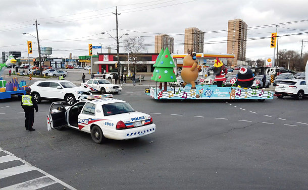 Parade floats going through an intersection blocked by police