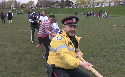A man in TPS uniform pulling on a rope with kids