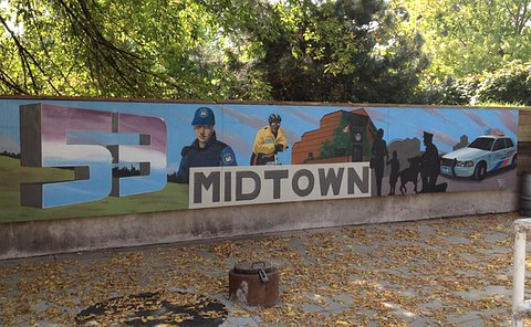 A large mural on a half wall with the number 53 and images of police officers and a community as well as a brick building