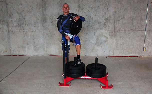 Man dressed in a blue sports outfit holding a cylindrical weight, with one foot on a metal sled that's loaded with more weights