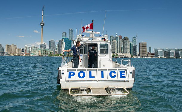 A man in marine uniform on a police boar with the Toronto skyline behind him, looking east.