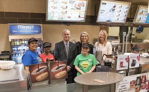Men and women behind a fast food counter