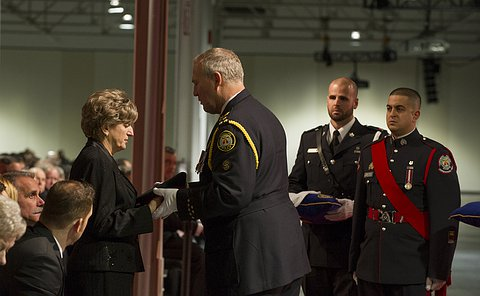 A woman looks down at the police hat she is being given by a man in Toronto police uniform as two other men in Chief's Ceremonial Unit uniform look on