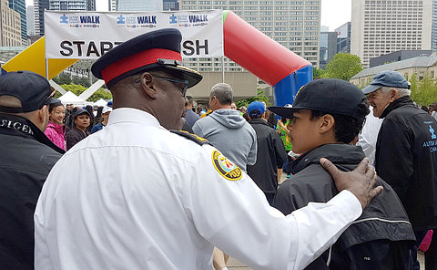 A man in TPS uniform with his arm around a teenage boy