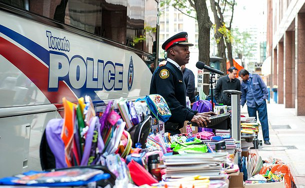 The chief standing in front of a bus, he is at a podium and around him are tables full of school supplies.