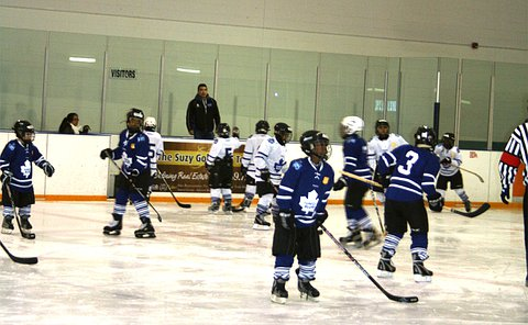 A group of boys in hockey uniforms on an indoor ice rink