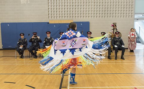 A girl in traditional Aboriginal clothing dances in front of people in TPS uniform
