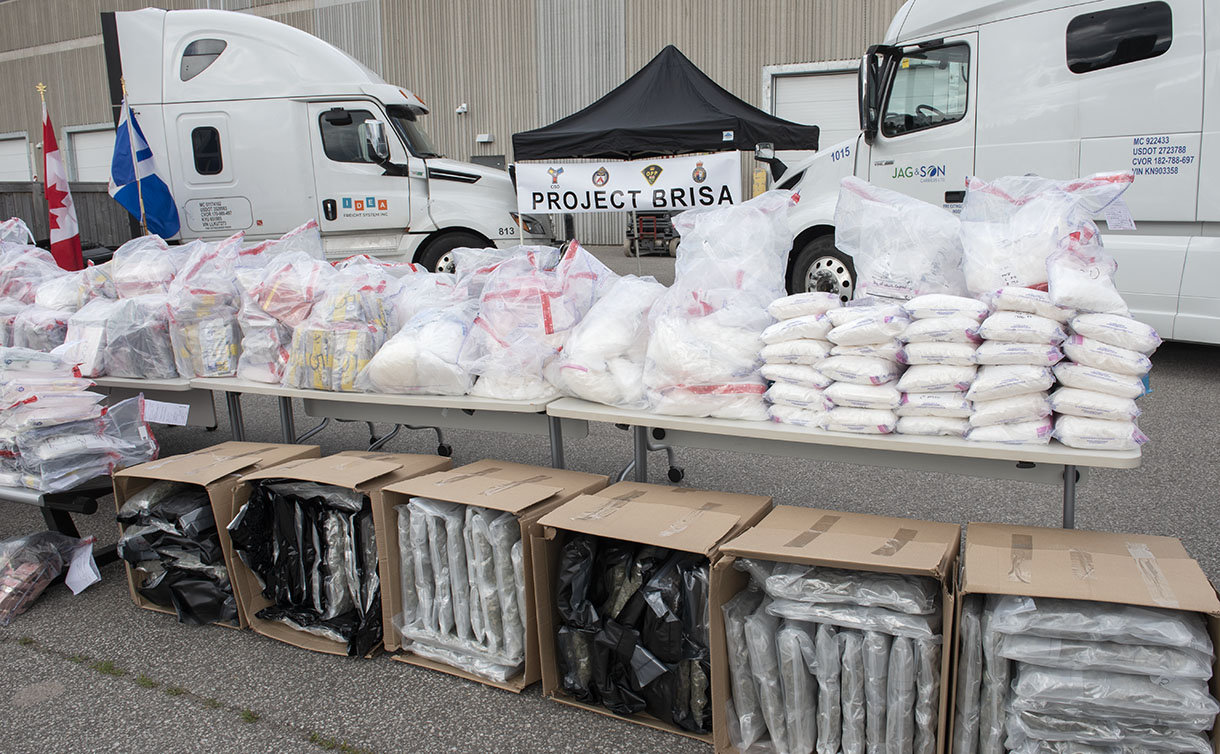 Tables of packaged drugs and two semi-trucks