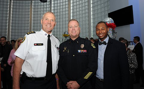 Two men in police uniform beside another man