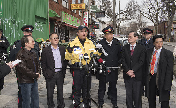 A group of men behind microphones, two in TPS uniform