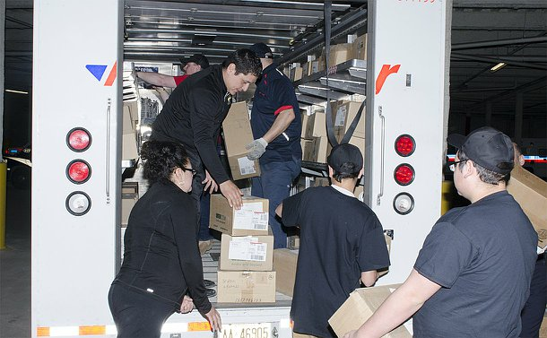 A group of people load a courier truck with boxes