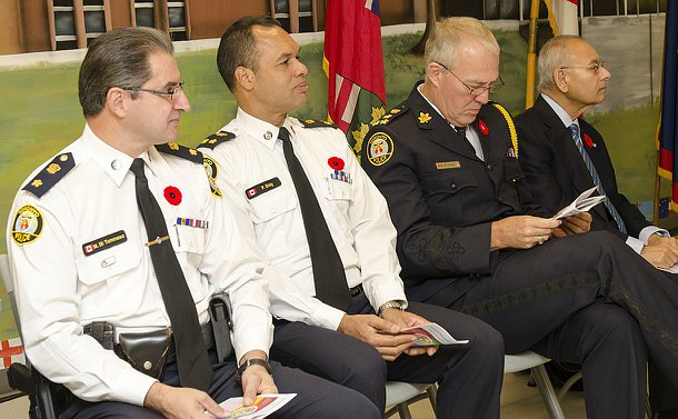 Three uniformed officers and one man in a suit sit side by side.