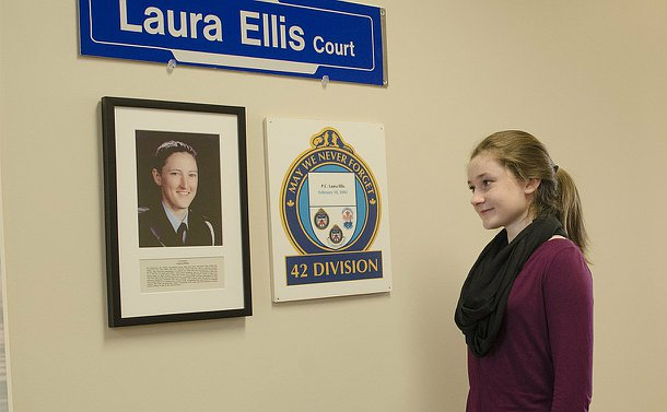 A girl looks at a plaque with a TPS logo and a photo of a woman in TPS uniform