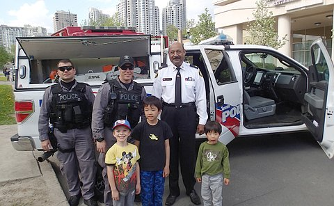 A group of men in TPS uniform with boys in front of a police vehicle
