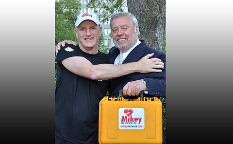 Two men standing together, one holds a yellow plastic box