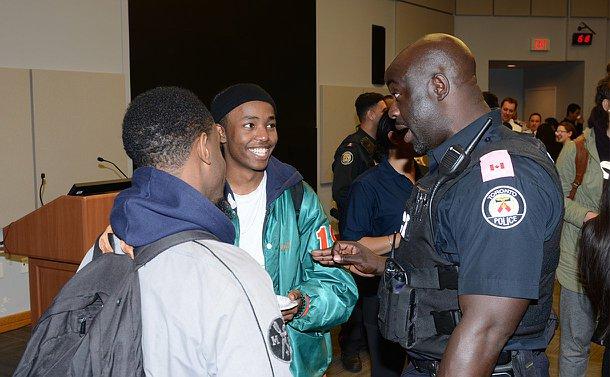 Two men speak to a man in TPS uniform