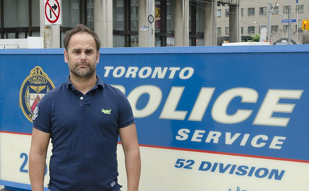 A man standing beside a TPS sign