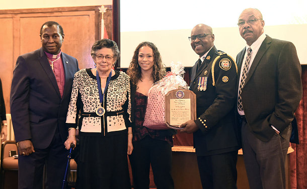 Man in a suit, two women one holding a gift bag, man in a police uniform holding a plaque, man in a suit