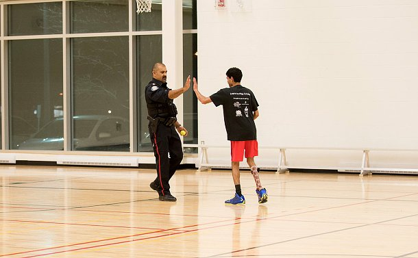a man in uniform giving a high fives to a boy