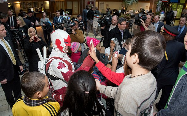 A man in a red costume high fives a child in a group of people