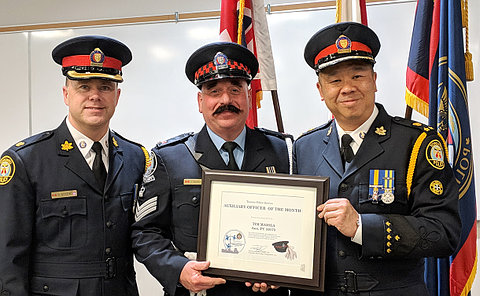Three men in TPS uniform, one holds certificate