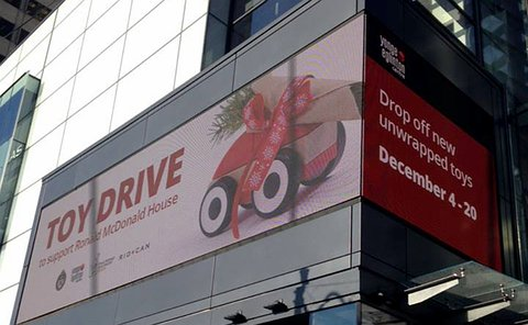 A large screen on a building advertising a toy drive