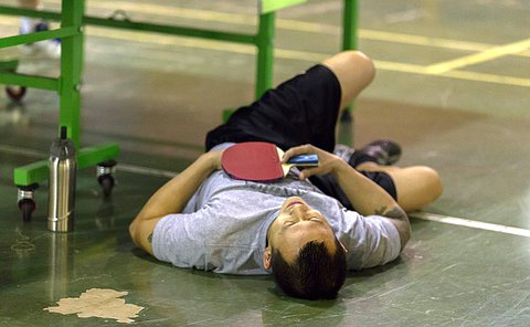 A man lays on the floor beside a table tennis table with the racket in his hand resting on his chest