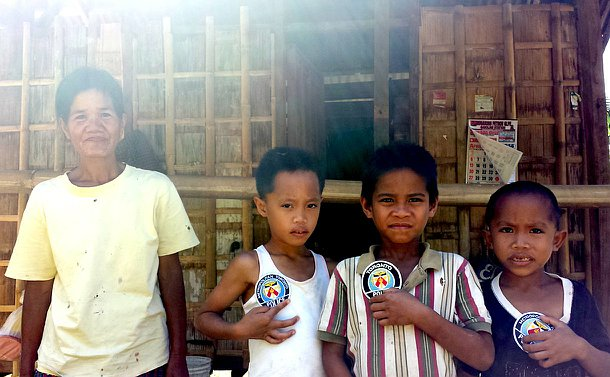A woman and three boys holding TPS patches in front of a wooden home