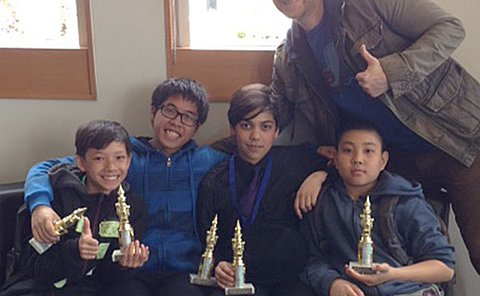 Students sitting with their chess trophies
