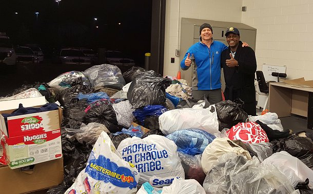 Two men give a thumbs up by a large pile of bags
