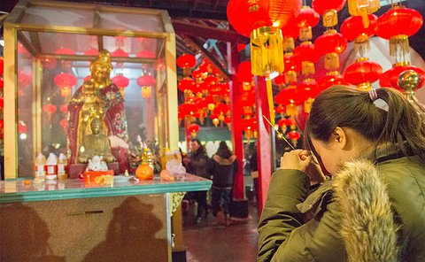 A woman holding incense bent over in prayer in front of an enclosed statue