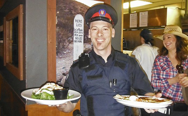 A man in TPS uniform hold two plates of food