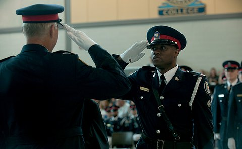 A man in TPS uniform is seen saluting another man whose back is turned to  the camera.