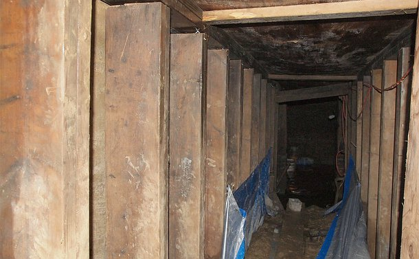 A tunnel framed by lumber with a dirt floor