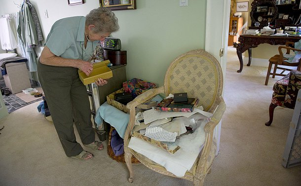 An elderly woman with an empty box in her hand, looking down at more empty boxes and pieces of paper.