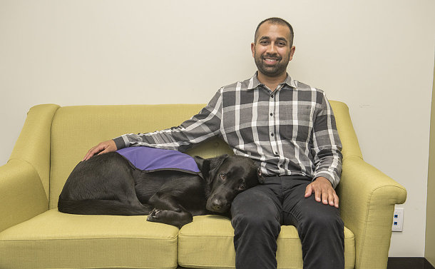 A dog lays beside a man seated on a couch