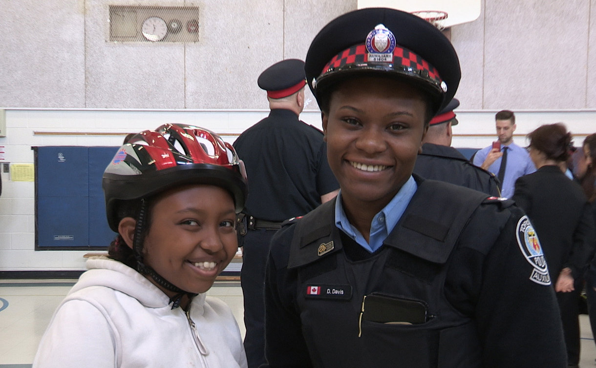 A woman in TPS auxiliary uniform with a girl wearing a bike helmet