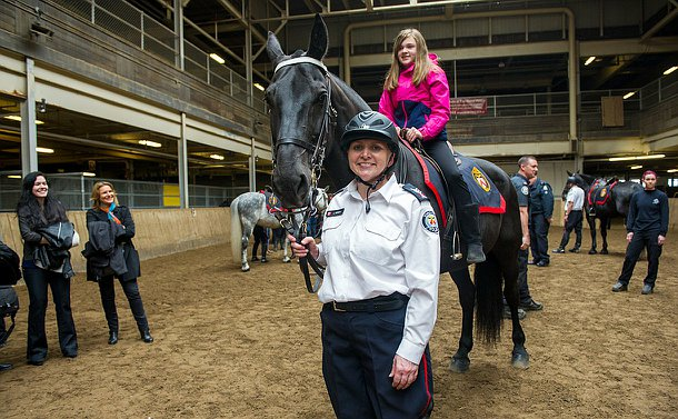 An officer unmounted uniform standing beside a horse while a girl sits on it.