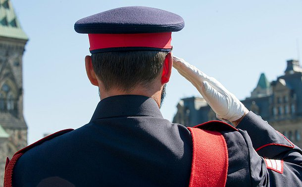The back of an Saluting and wearing a uniform.