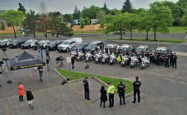 A large of of OPP and TPS vehicles and officers being filmed by video camera operators