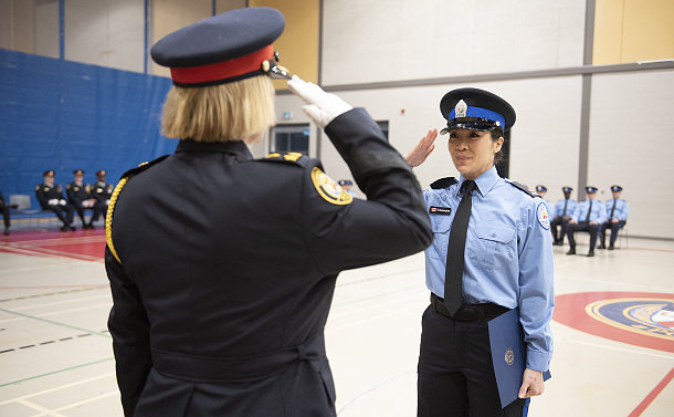 A woman in parking uniform saluting