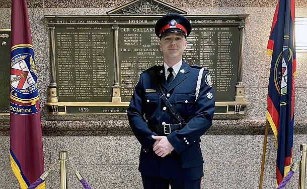 Man in a police uniform is flanked by two flags and stands in-front of a wall with a plaque containing an honour roll of fallen officers