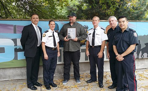 Four people in TPS uniform, and two others, one holding a plaque stand in front a half-wall with a mural on it
