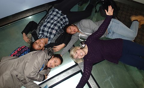 A group of four women lie on a glass floor