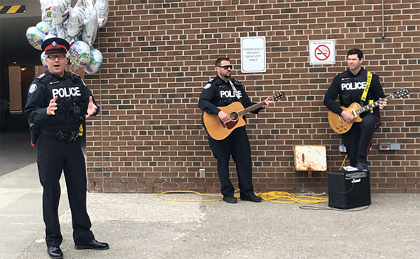 Three men in TPS uniform, two hold guitars